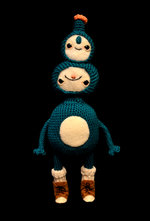 Blue standing doll with two faces black background